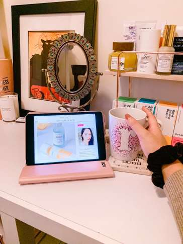 If you're trying to get in some self-care while social distancing, make it productive by starting a blog or a youtube channel. Imge description: Vanity with an antique mirror and shelves of skincare products. On the vanity sits an ipad with a screenshot of the Levitate Beauty home page. A hand can be seen holding a mug of tea.