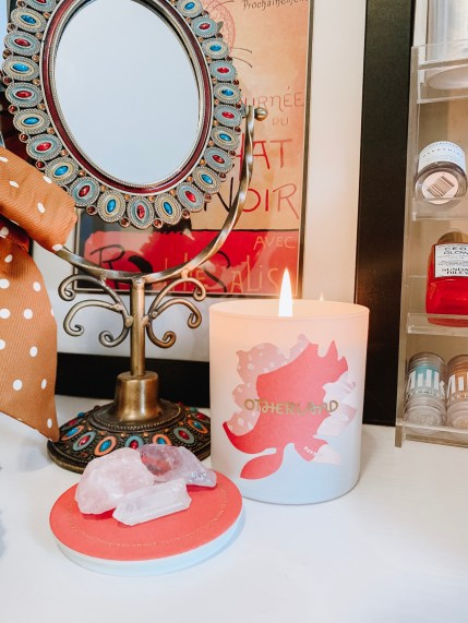 Otherland Daybed candle on a vanity with an antique mirror. Surround the candle is an antique mirror, a shelf of skincare products, and several quartz and amethyst crystals from Sunday Forever. Aromatherapy is a great way to relax and practice self-care during self isolation.