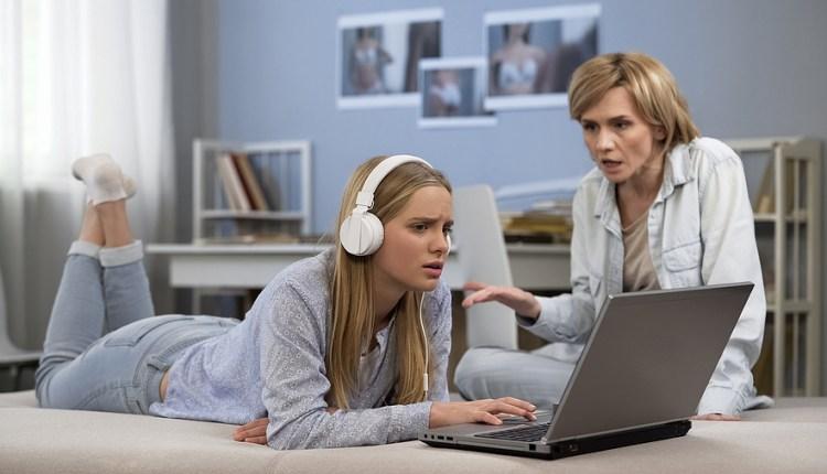 Teenager In Headphones Ignoring Mother, Surfing Net, Difficult P