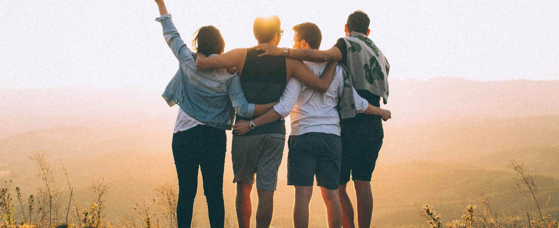 anonymous friends standing together at sunset in mountains