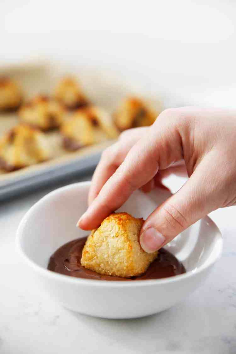 Dipping coconut macaroon in melted chocolate.