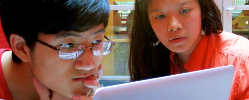 Photo of two students looking intently at laptops