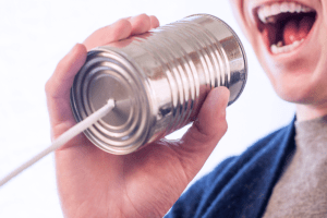man speaking into tin can with cord