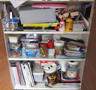The Crafting Cupboard, yellowreadis.com Image: Bookcase full of craft supplies in containers, slightly disordered