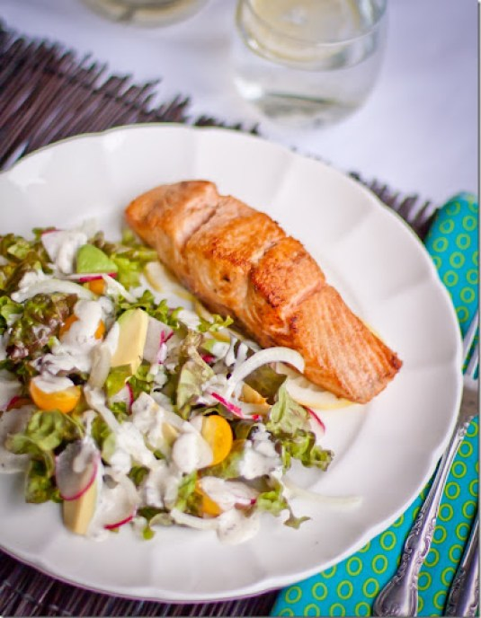 Top view of fresh salad with homemade buttermilk dressing with buttered salmon on a white decorative plate.