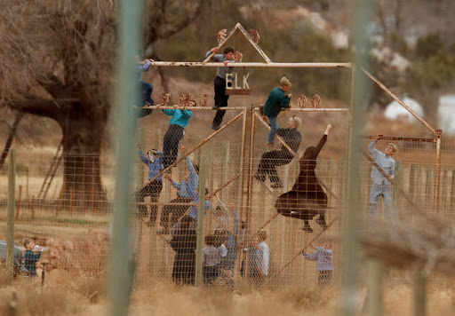 Children climbing a fence at what was once a thriving community zoo in Hildale, a town where many residents are members of Warren Jeffs' FLDS church