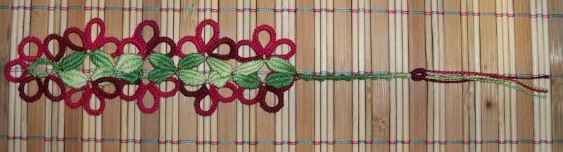 Señalador con clunies verdes en el centro y borde de anillos bordó
