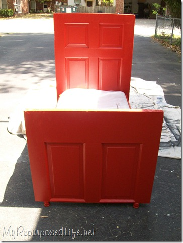 red toddler bed made from a door