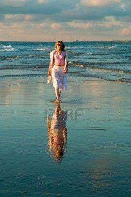 Mujer joven acercándose por la orilla del mar.