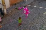 Piniata hunging over a cobblestone street in Colonia San Rafael in San Miguel de Allende, Mexico. Underneath Alex dancing...