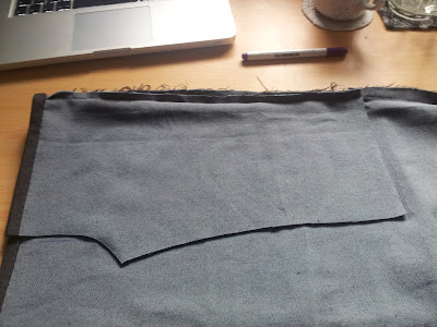 denim material on desk, one leg of trousers cut and being used as pattern for second leg