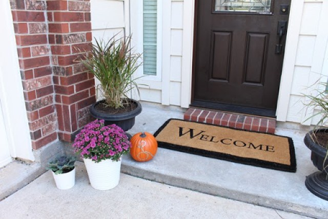 Huge Large Welcome Mat Front door fall Porch Scape purple mums and decorative cabbage. Black urn with fountain grasses all drought resistant for hot climate fall decor. Domesticability.com