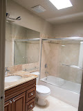 Guest bathroom with travertine tiles, bathtub, and granite countertop. Both full bathrooms have skylights in the ceiling for natural light