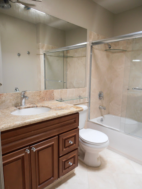 Guest bathroom with travertine tiles, bathtub, and granite countertop.