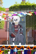 Paper cut-outs and a skeleton riding a horse poster on display in front of a parish church (Parroquia) near the central square (Jardin Allende) in San Miguel de Allende, Mexicco on the Day of the Dead (Dia de los Muertos).