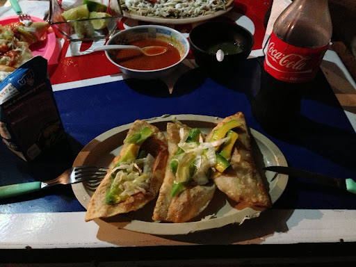 Homemade empenadas (2 chicken and 1 pork) at a comeador (someone's front yard) in Laguna Milagros. My four empenadas and the coke cost $2.