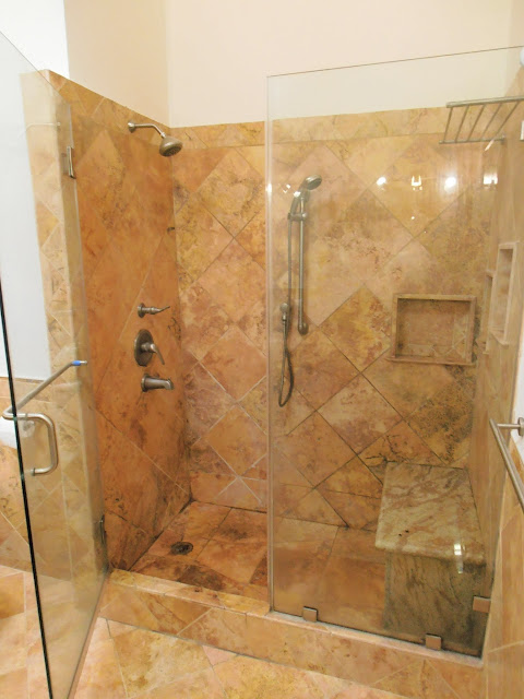 Master Bathroom - Oversized shower with 2 shower heads and a granite bench and stone travertine tiles on floor and walls
