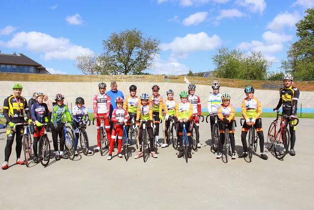 groepsfoto van de pistetraining met Eric Van Lancker, Kris Hanne, Lorenzo Louagie en de jonge wielrenners