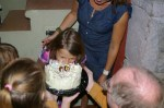 The local custom is for the birhday kid to bite into the cake after blowing the candles.
