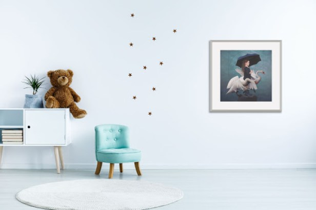 Simple art hangs in a child's room with a teddy bear on edge of a white dresser