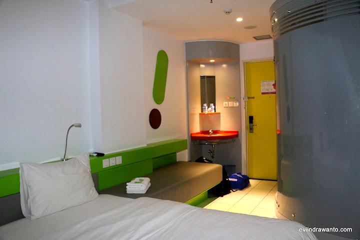 Ranjang, sofa, colokan listik, wastefel dan kamar mandi di sebelah kanan yang disainnya futuristik