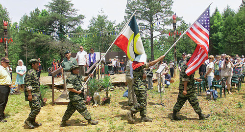 PARTNERS — The flags of both the U.S. and Montagnards are carried away after completion of official ceremonies at a Montagnard gathering near Asheboro in 2005. This year's Montagnard Memorial Event, 'Dega Days,' kicks off at noon on Saturday with festivities that include a dinner, tribal dances beginning around 1:45 p.m., a market with handmade crafts, a museum of artifacts and visits through a longhouse. The event is free and open to the public. (Paul Church/The Courier-Tribune).