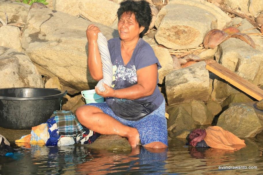 Ibu yang tinggal di seberang sungai sedang mencuci baju