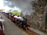 A steam train passes on the other side at Irton Road Station