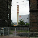 Power station behind old buildings and gated pigpens and trash container on the left.