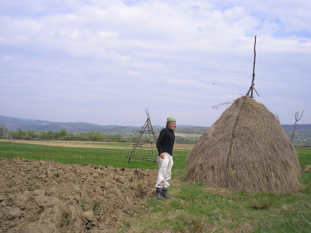 Me next to some haystacks in Romania. I suppose that in twenty years Romanians will wrap their hay in cellophane like we do.