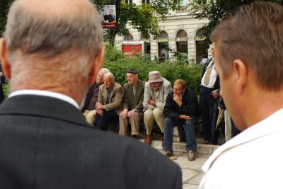 Old chaps watching a public chess game