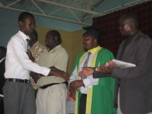 Receiving an award from the Headmaster (robed in University of Zambia dress) and a present (notice the newspaper wrapping) from the District Head.
