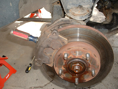 It might seem a little redneck, but take a sturdy screwdriver and stick it through the opening in brake caliper and into one of the openings along the outside of the brake rotor.  This will keep the hub from turning in the next few steps.