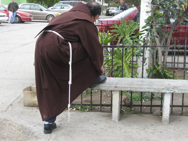A monk trying his shoe.