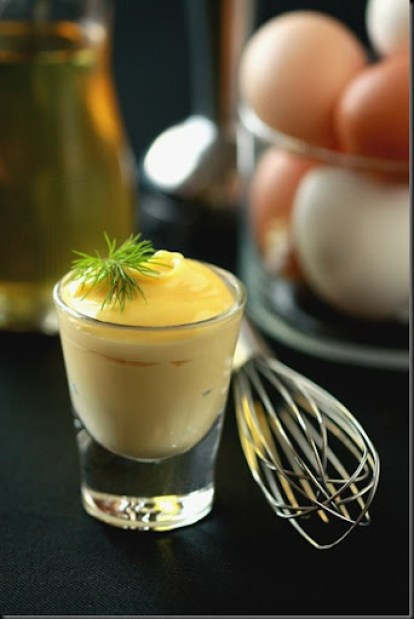 Homemade mayonnaise in a shot glass topped with greens and a whisk with eggs and oil in the background.