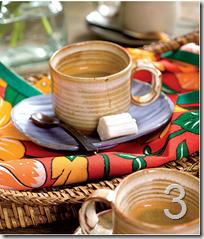 Uma cena bonita: a xícara sobre o pires, a balinha de coco e a colher. O charme, entretanto, repousa no guarda-napo feito de chita. Olhe só que efeito bonito.