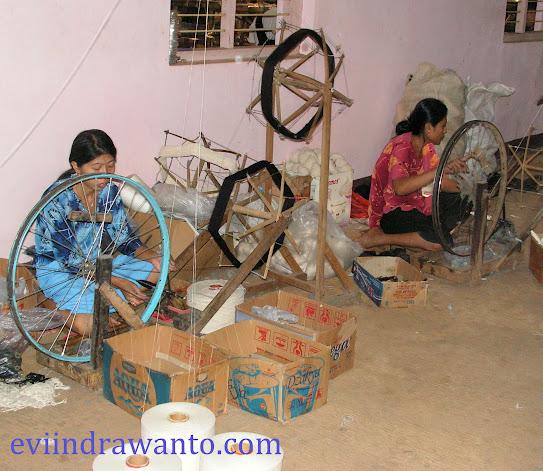Pekerja menggulung benang di workshop tenun troso