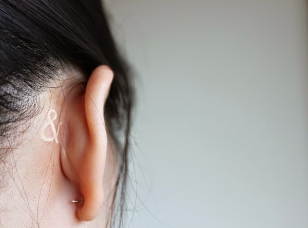 small music symbol tattoo behind ear
