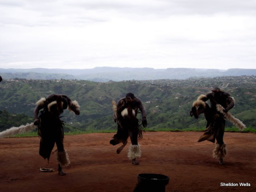 zulu warriors dance against the backdrop of the valley of 1000 hills, outside durban, south africa