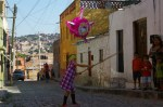 Nadia swinging a broom stick on a cobblestone street of Colonia San Rafael in San Miguel de Allende, Mexico.