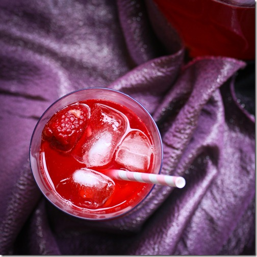 Kompot beverage with ice and floating raspberry
