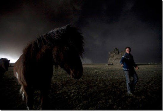 Farmer Thorarinn Olafsson tries to lure his horse back to the stable as a cloud of black ash looms overhead in Drangshlid at Eyjafjoll on April 17, 2010. (REUTERS/Ingolfur Juliusson) #