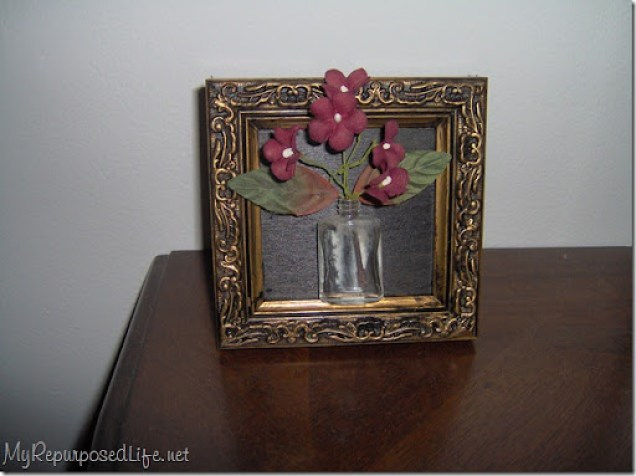pretty gold frame with an old bottle
