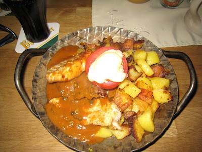 Three kinds of meat, fried potatoes, pepper sauce with a tomato and cheese
