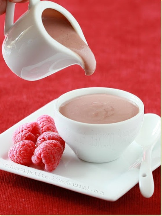 Berry curd being poured into a white decorative bowl that sits on a white decorative plate with raspberries and white spoon.