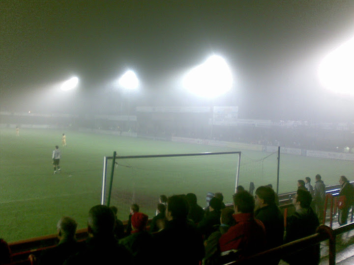 Rushden fans look on as the fog continues to thicken.