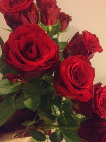 A dozen red roses in a vase