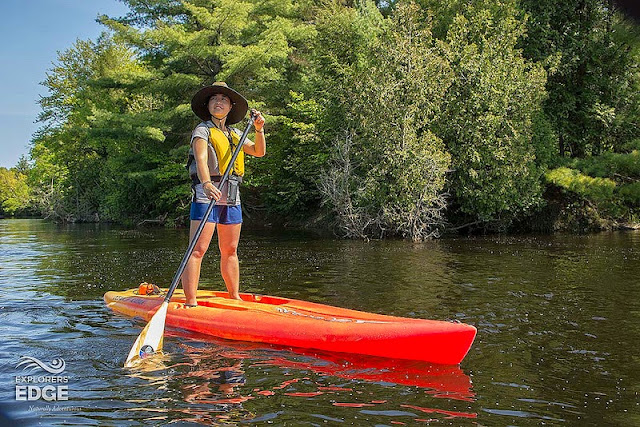 Jill on a stand up paddle board fighting the current of Muskoka River