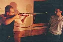 photo of a scene, image of Joseph Williams as Mickey pointing a rifle at Dean, played by Juan Modinger