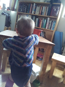 Leon, from behind, wearing mitred baby jacket and playing with something at a table
